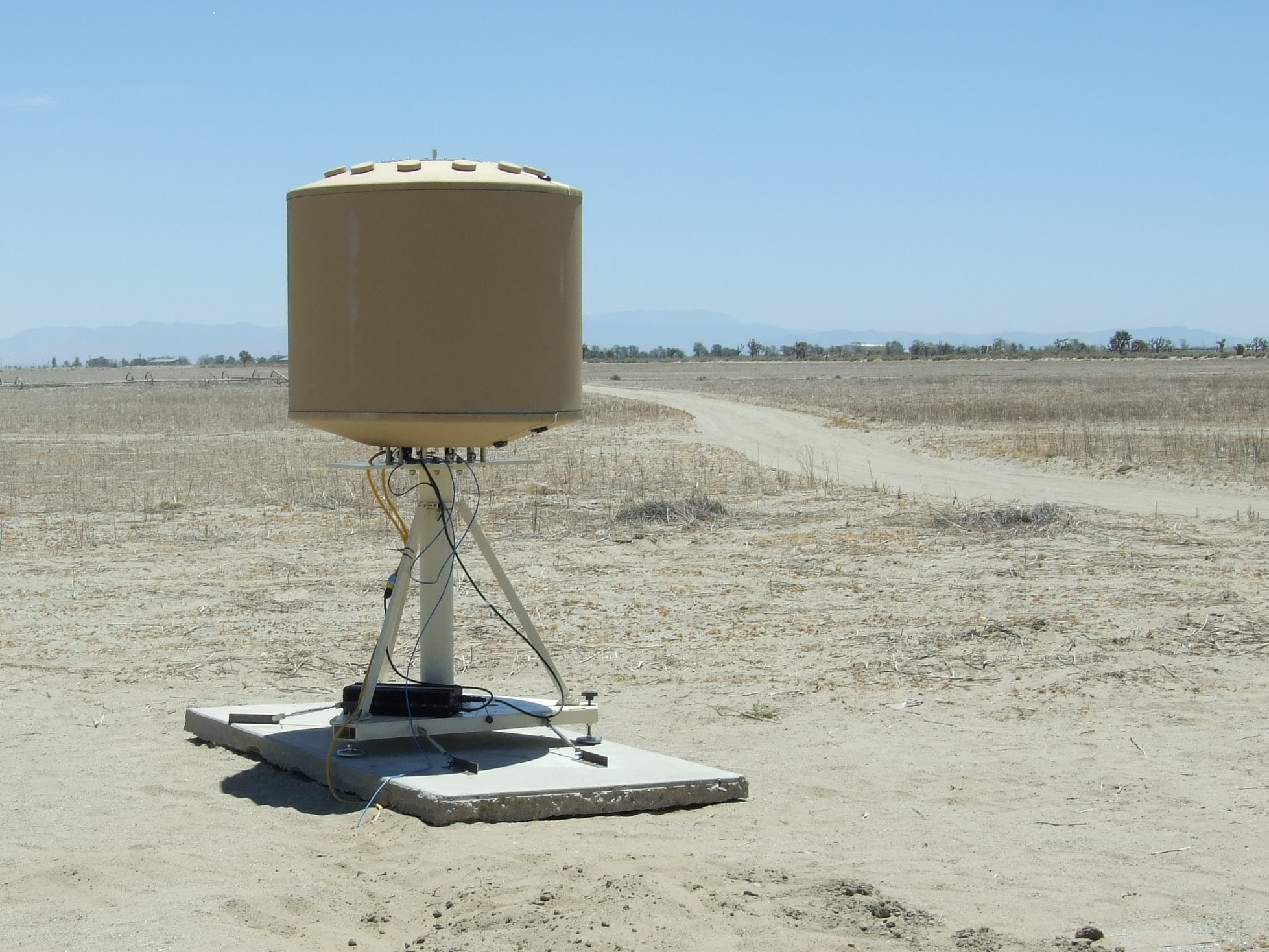 SRC's AN/TPQ-49 radar with LSTAR software in a rugged tan enclosure in front of a rugged desert landscape
